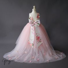 The Lili dress is a stunning, delicate dress that will make your little girl feel like a princess. It features a soft, pink floor-length tulle skirt. There is a