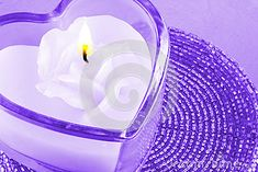 A closeup of a glass candle holder with a white wax rose candle.