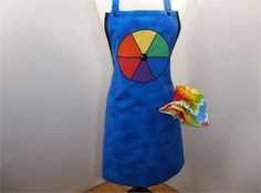 A bright blue fabric is the background for this artist apron. The bib is trimmed in black bias tape with black buttons used as accents throughout the apron. A large color wheel is appliqued onto the bib area of the apron. There is one pocket complete with a bright tie-dye bandana to serve as a paint rag. This smock will help to protect your clothes while you create your next masterpiece. The length from the top of the bib to the bottom hem is 33. The width is 28 and each of the two ties is…