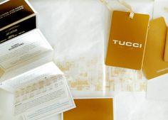 Sistema de packaging integral de Tucci, temporada primavera verano. 5 medidas de bolsas, combinación de dorado y blanco, hang tag, cuidado de ropa, papel seda, bolsa producto. Realizado en Estudio FBDI