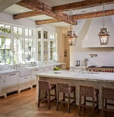 white cabinets, white marble countertops, rustic wood beams