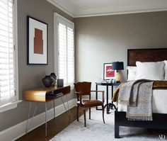 In this Raleigh, North Carolina, home designed by S. Russell Groves, the guest bed, dressed in RH matelassé linens, is paired with a vintage Eames-style desk. The throw is by Anichini.
