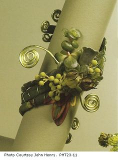 Apple Green aluminum wire and the same color metallic wire are used with florets of Nigella for this unique arm band.  Interesting foliages including equisetum, variegated leucadendron, berzelia, Chinese sedum and a small piece of Succulent plant, were incorporated into this cool looking design.  This corsage would also work well being worn on the arm or wrist.