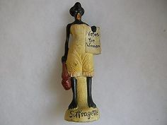 Satirical figure re: the Women's Suffrage Movement. eBay, Jun 2015, asking $999.99. ~~Seller's description:  HOW RARE IS THIS A BLACK WOMEN AT THAT TIME ASKING FOR THE RIGHTS FOR WOMEN TO VOTE THERE IS ONE TINY CHIP FLAKE ON THE BOTTOM OF HER SIGN SEE PHOTO WITH MY THUMB THAT WERE THE FLAKE IS SHE IS DIRTY AND NEEDS A CLEANING BUT I'AM LEAVING THAT FOR THE NEW OWNER  BUYING THAT WAY I'AM NOT STARTING IT CHEAP BUT IF IT GETS A BID IT'S SELLING WHEN WAS THE LAST TIME YOU SEEN ONE MEASURES 7…