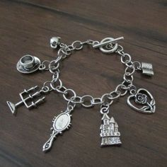 This bracelet is inspired the Disney movie Beauty and the Beast. It features antique silver book, heart rose, castle, mirror, candelabra, teacup,