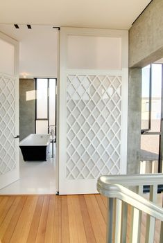 Modern trellis panel doors with opaque glass. Designed by Roy McMakin.