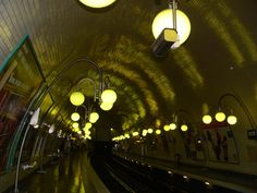 The Cité station lies underneath the Île de la Cité. The soft light from the low-hanging globes of the art nouveau street lamps bounces off the polished tiled ceiling and slick floor to great effect.