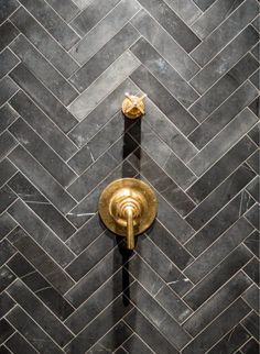 Trending now: Dark gray subway tiles set in a herringbone pattern combined with brass bath fixtures.