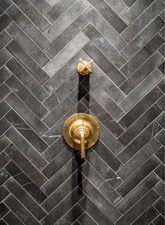 Trending now: Dark gray subway tiles set in a herringbone pattern combined with brass bath fixtures.