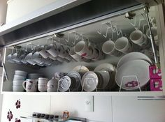 Ganchos para pendurar xícaras e apoios para pratos multiplicam o espaço do armário de cozinha. | 24 truques de organização que vão tornar sua vida melhor