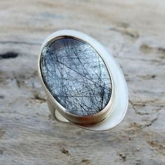 This statement ring is constructed of sterling silver and holds an oval black tourmilated quartz stone. It is totally unique and trully one of a