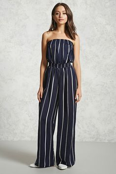 A woven jumpsuit featuring a pinstripe pattern, a strapless design, a smocked bust and waist, and a wide-leg cut.