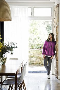 Owner Sarah Crennan stands in front of the bi-fold doors that open onto the back terrace and garden area.