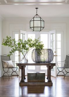 Airy entry hall with a Suzanne Kasler-designed console table and wrought iron accents.