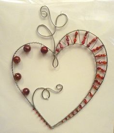 Handmade silver tone wire wrapped heart, with assorted red beads. Unique design.