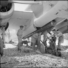 Airmen ground crew, assisted by soldiers and sailors, load a Mark XII aerial torpedo into the bomb bay of a Bristol Beaufort Mark I at Luqa, Malta, in preparation for a sortie against the Italian naval force threatening the 'HARPOON' Convoy.