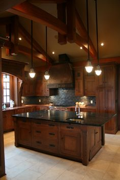 Love the rich, dark, wood. Very warm and inviting. Dark counter tops, light tile floor.