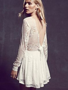 "Lolo Lace Fit and Flare Dress | Long sleeve lace fit and flare mini dress with deep-V back, featuring a bow. Fully lined, with straight sheer sleeves.  *By For Love & Lemons   *Derived from those sun-soaked ""Lemonade Stand Days,"" designers, owners, and BFF's Gillian Mahin and Laura Hall are the masterminds behind For Love & Lemons. Based in Los Angeles, the collection is anything but conventional. For Love & Lemons is a brand for that girl who doesn't follow trends, she makes them."