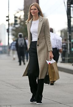 Cool and casual: Karlie, 23, nailed transseasonal styling in her comfortable ensemble which comprised black high-waisted trousers, cropped white jersey top, nude blazer coat and adidas trainers