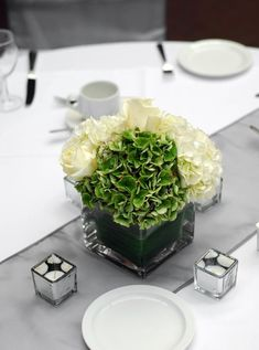 Hip to be Square  If you want a modern look without going to extremes, consider using square elements throughout your reception tables. Using square vases for arrangements alongside square tea light holders adds a hint of hip to otherwise traditional wedding decorations.