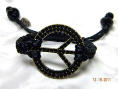"""60 Something"" is a black braided bracelet using 2mm satin cord. It features a 2"" black rhinestone peace symbol in the middle. There is an adjustable slip knot with drawstrings that have black faceted end beads.    PRICE: $25"