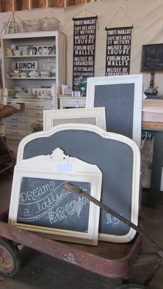 Ignoring the wagon of chalkboards, I LOVE that dresser in the background with the wire baskets and all the dish ware.