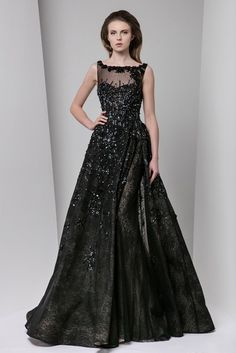 Black A-line evening dress with a side slit opening on a sheath lace underskirt, with semi sweetheart illusion neckline and patchwork embroidery.