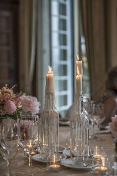 Table candle ideas. These clear glass wine bottles used with stick candles are a great way of creating a romantic and inexpensive table display. We love the way the candle wax drips down the bottle over the course of the evening.