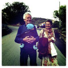 Happy grandparents carrying grandson in JPMBB baby wrap.