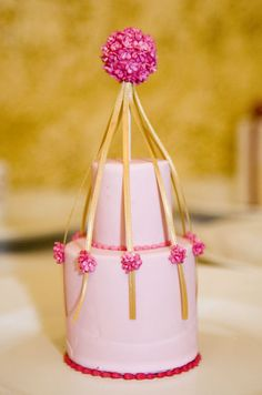 Tiny pink flowers and gold ribbons add a festive touch to  this light pink individual cake