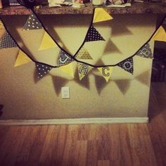 Jacob's bunting for baby shower and baby's room. Made of fabric and backed with wool felt (used yellow zip zag to sew together) The line is black bias tape and hand cut wool felt letters that were appliqued.