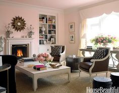 In a San Francisco house designed by Stephen Shubel, this living room's walls are painted Benjamin Moore's Bridal Pink, a soft color balanced by the deep browns and the earth textures in the room. Hanna chairs in leather flank an antiqued brass drum table, both from Oly. The mirror is by Two's Company. The girandoles are 19th-century French. Natura carpet in Seagrass is from Stark.   - HouseBeautiful.com
