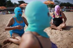 Women, wearing nylon masks, rest on the shore during their visit to a beach in Qingdao, Shandong province July 6, 2012. The mask, which was invented by a woman about seven years ago, is used to block the sun's rays. The mask is under mass production and is on sale at local swimwear stores. [Photo/Agencies]