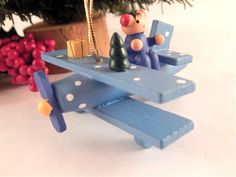 """Wooden Airplane Christmas Tree Ornament 1990's Hand Painted Wooden Glider Blue prop plane, glider, airplane Wooden pilot, christmas tree and gift Flat base allows use as a figurine 3"""" h x 1 1/4"""" l x 3/4"""" w 2 1/2"""" gold cord hanging loop A charming ..."""