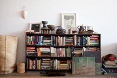"""On top of the bookshelf is a tall bowl by Andrew Kazakes (Wu's ex-boyfriend) next to a wood-handled bowl picked up on a road trip driving around Sri Lanka. """"It was the only souvenir I got. I went with Andrew and my best friend, Anat, and our lives were just beginning to fall apart, though we didn't know it yet. We got in a car accident when the brakes on the rental car stopped working on a windy mountain road, and the guy whose car we rear-ended ended up taking us out for tea and sweets…"""