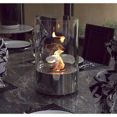 The decorative indoor fireplace is the perfect accent to any table, in any setting. This portable tabletop fireplace features a polished stainless steel base and stunning tempered glass cylinder encasing the flames.