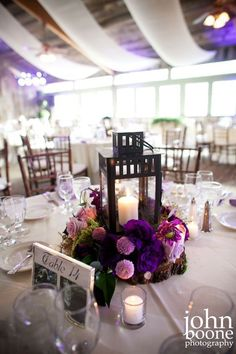 Elegant rustic chic purple flower wedding reception centerpiece with classic lantern decor; Featured Photographer: John Boone Photography