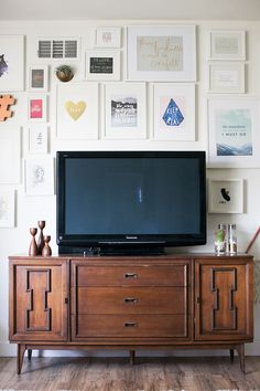 Mid-century console media center with gallery wall around TV