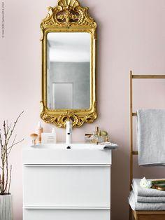En GODMORGON kommod i stilren design med högblank front har fått sällskap av en gammal vacker guldspegel. BRÅVIKEN tvättställ, DALSKÄR tvättställsblandare, RÅGRUND stol med handdukshängare, HÄREN handdukar.