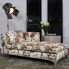 Add contemporary style to your home or office with the look of cowhide. Upholstered in an animal-friendly printed cow-hide fabric with wood legs finished in a faux aluminum metallic finish, this chaise will liven up any space.