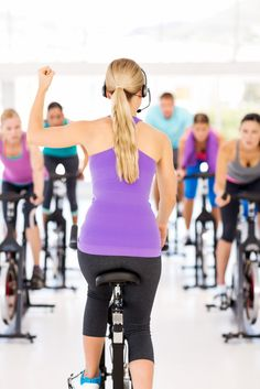 an instructor in a group fitness class for spinning
