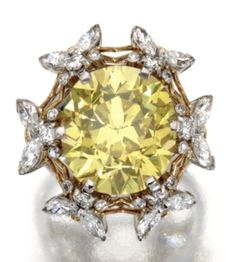 PLATINUM, 18 KARAT GOLD, FANCY VIVID YELLOW DIAMOND AND NEAR COLORLESS DIAMOND RING, SCHLUMBERGER FOR TIFFANY & CO., 1972 The cushion-shaped diamond of fancy vivid yellow color weighing 11.13 carats., framed by bees set with small round and marquise-shaped near colorless diamonds weighing approximately 2.05 carats. Sotheby's.