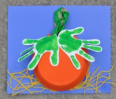 These pumpkins have handprint leaves - a fantastic Halloween or Thanksgiving project to do at home with your preschooler or in a preschool classroom.  It incorporates both sensory and fine motor elements: making hand prints, scrunching up paper bags, and cutting and gluing yarn.