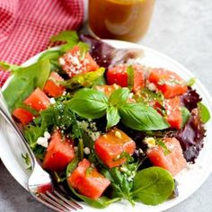 Watermelon feta salad is perfect for summer - watermelon, basil, feta over mixed greens, topped with balsamic vinaigrette.