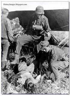 Not a very nice man. A Waffen SS soldiers kicks a captured Russian pilot. Kursk, 1943.