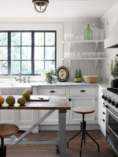 Kitchen    The late-1800s Belgian butcher's table, now a kitchen island, still bears traces of newsprint from the table's hardworking industrial days. Stanton left the Carrara marble counters unhoned to show wear. The walls are painted Country Stove White by Ralph Lauren.