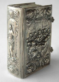 A silversmith skillfully made this silbereinband, or solid silver binding, in the late 17th century. The artist, possibly from Bavaria, executed the design in relief. Christ, holding a cross, is represented on the spine, with a snake and a skull at his feet, symbolizing his triumph over Satan & death. On the front of the binding is a beautiful interpretation of the Last Supper, similar to the style of Italian sculptures of the sixteenth century. 2 silver clasps are adorned with floral…