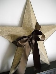 mod podge a piece of burlap on a rusty thrift store star, trim it with twine on the edges and a glue gun, and wrap a brown satin ribbon around it ... it can't get much easier ... spenceandheidi b-is-for-burlap