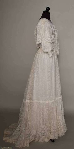 """WHITE LACE SUMMER TEA GOWN, c. 1904    2-piece, constructed of Val lace yardage, narrow Val lace trim & chemical lace appliques, mono-bosom bodice, V neck, elbow length sleeves, trained skirt, deep hem flounce of repeating concentric U shape narrow lace ruffles, both pieces fully lined inwhite cotton net, B 36"""", W 27"""", Skirt L 42""""-48"""", (lace neckband possibly replaced) excellent."""