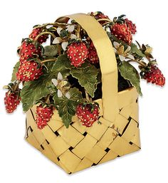 A SILVER-GILT AND ENAMEL TABLE ORNAMENT, BY CARTIER. Modelled as a basket of wild strawberries, the woven silver-gilt punnet filled with an abundance of red enamel fruits, among green enamel leaves interspersed with white flowers each with a green glass centre, circa 1950, 8cm high. Signed Cartier